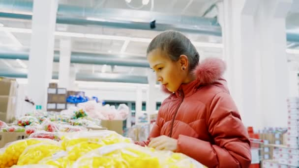 Young girl in a winter jacket in a supermarket chooses yellow dragees.