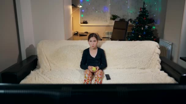 A young girl sits on a sofa and watches TV.