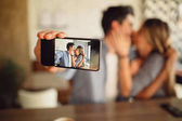 Couple taking selfie with rear camera while kissing in internet cafe. Shallow focus on mobile.