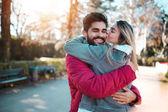 Mladý atraktivní muž objímá svou krásnou přítelkyni. Valentines day koncept.
