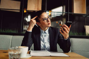 Worried businesswoman with eyeglasses holding smart phone, taking notes. Girl in cafe. Business, online business, remote office concept.