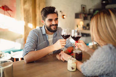 Romantic couple clink glasses with red wine and celebrating Valentine's day or anniversary.