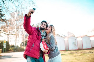 Attractive couple while making selfie. Man surprising his girlfriend with a gift. Couple in love. Valentine's day.