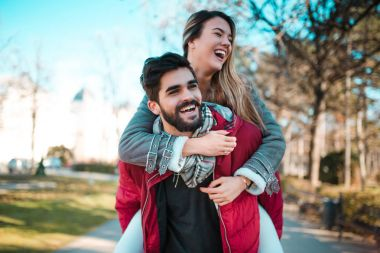 Couple in love having fun in the park. Man giving piggyback to woman. Young adults girlfriend and boyfriend hugging happy.