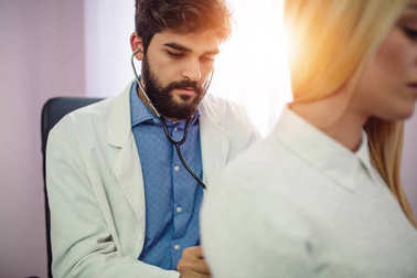 Doctor examining patient with stethoscope in medical office. Doctor using stethoscope to exam man patient heart. Portrait of handsome male doctor examines a patient with stethoscope.