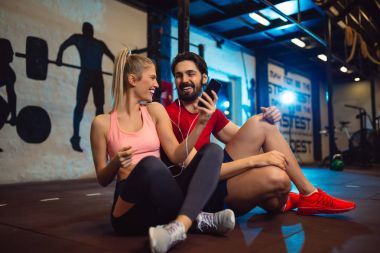 Fit couple in modern crossfit gym with smartphone listening to the music.