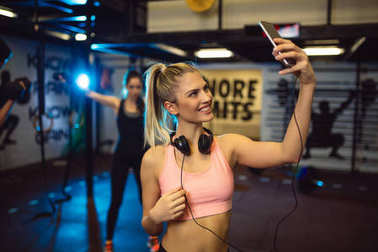 Smiling young sportive woman with headphones making selfie photo