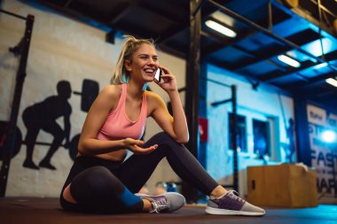 Smiling girl sitting on floor and using smartphone in gym.