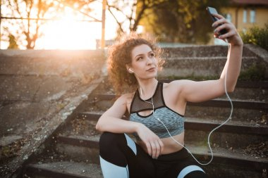 Young woman in sportswear getting ready to start running with favorite music on earphones
