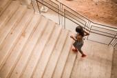 Fotografie Mladá africká americká žena běží nahoru po schodech