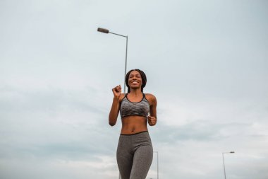 Healthy young african american woman running in urban environment