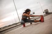 Fotografia Ragazza afro-americana sta allungando la gamba in strada dopo lesecuzione