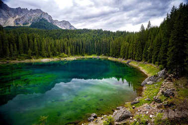 Lake Carezza is a small alpine lake located in the upper Val d'Ega at 1.534. It is set among dense forests of fir trees and is located beneath the slopes of the Latemar massif, which is reflected in its crystal clear water. Trentino Alto Adige. Italy
