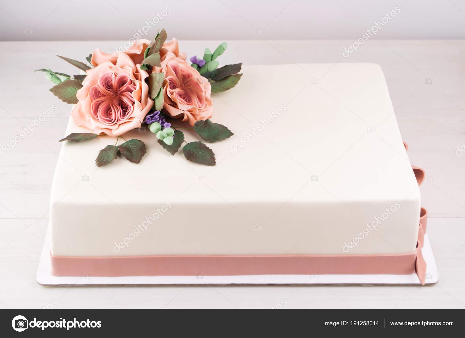 Arte rettangolare torta decorata con fiori rosa e foglie verdi da mastice  su una tavola di legno bianca. Foto per un menu o un catalogo di prodotti  dolciari