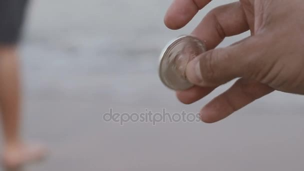 mans hand holding silver Bitcoin on seashore background