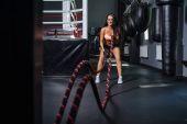 Žena s bitvou lana cvičení v posilovně. Mladá žena trénink v tělocvičně tmavé