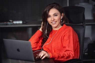 Successful young woman sitting at table in office, working on her laptop.