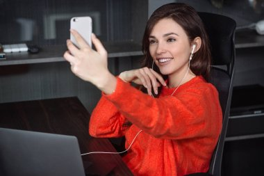 The girl uses smartphone and shares selfie