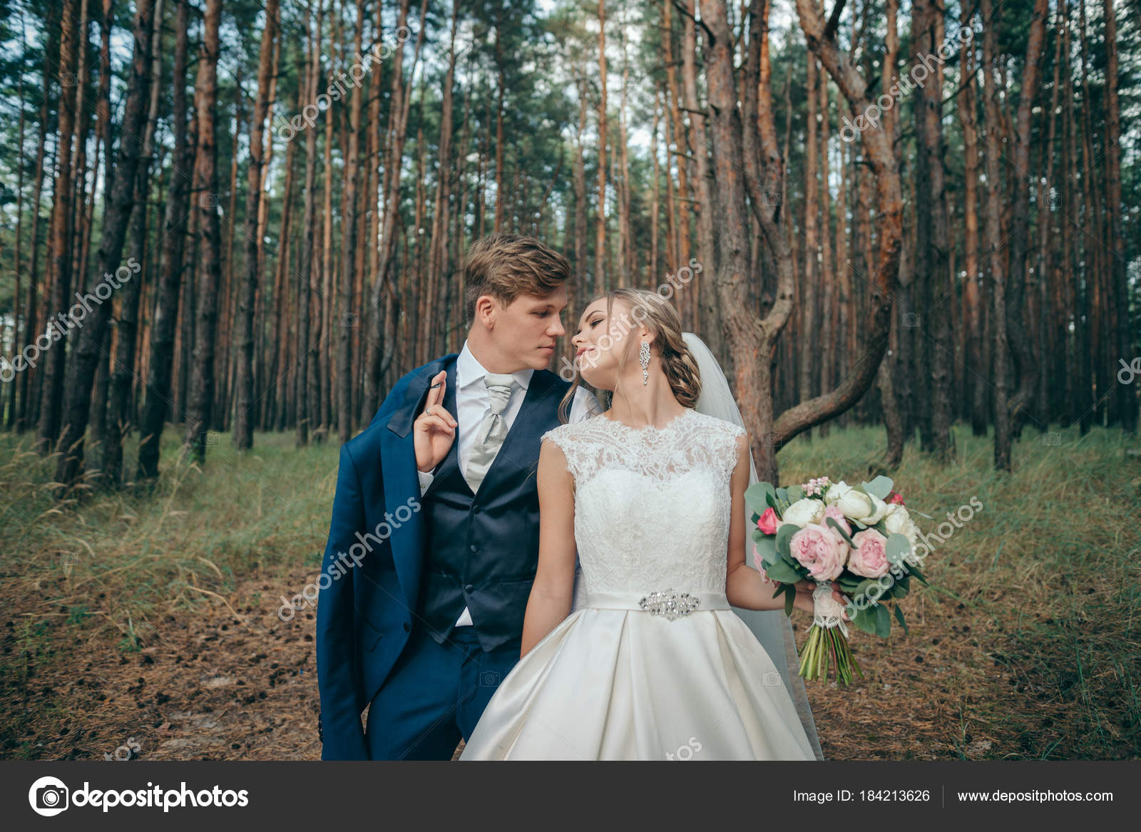 The bride and groom in wedding dresses on natural background ...