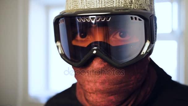 Muž, který je zloděj a lupič, vloupání do domu prostřednictvím zadními dveřmi, zatímco na sobě masku a šel směrem k fotoaparátu se podívat přímo do objektivu skončit a široké oko