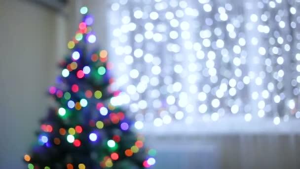 Vánoční stromeček zdobený třpytivý vánoční stromeček hračky a zářící světla. Strom není v centru pozornosti. Bokeh