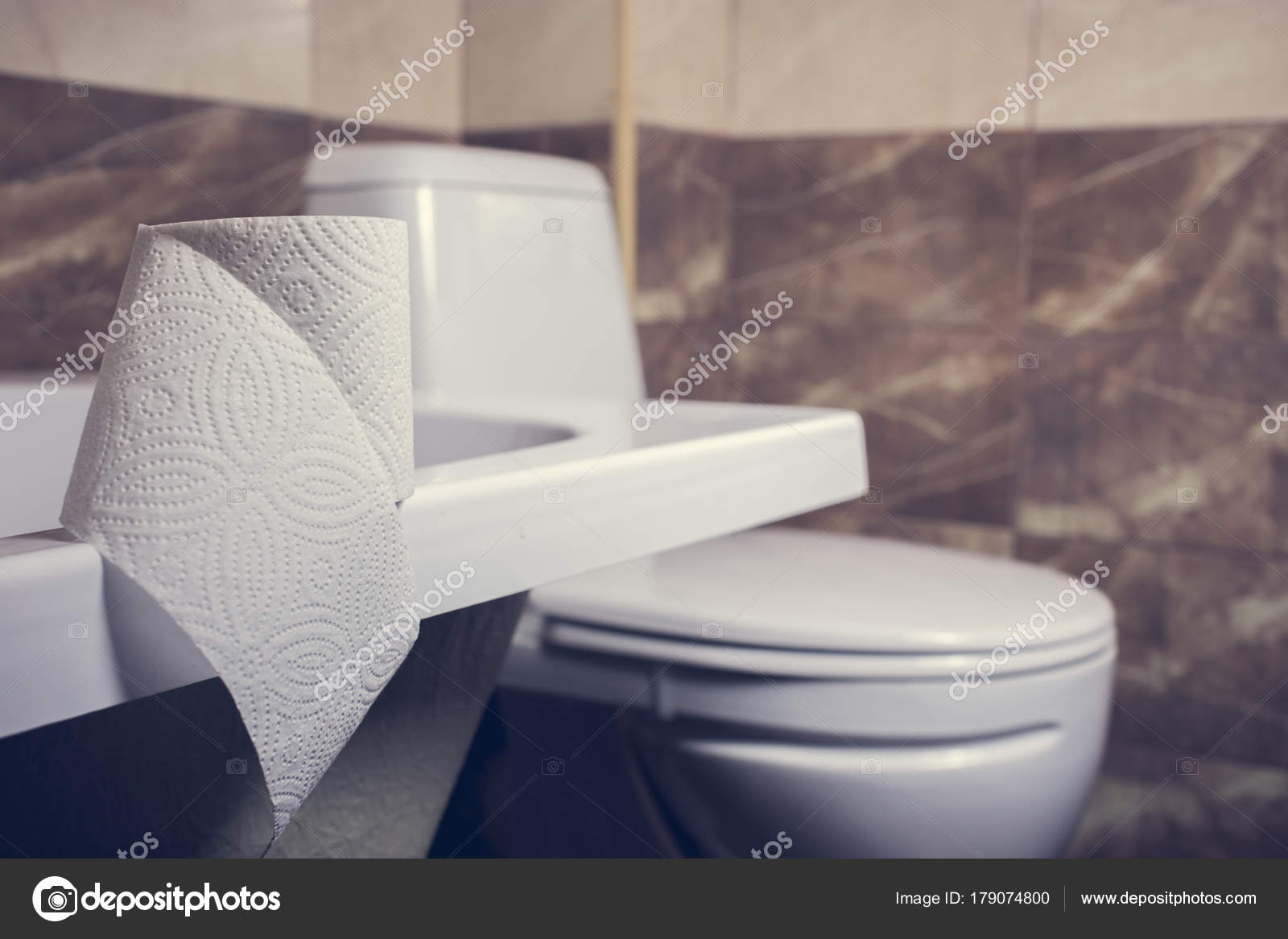 A Roll Of Toilet Paper On The Background Of Toilet On The Edge Of