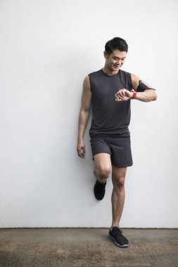 Asian man running  using his smartwatch