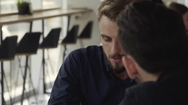 Két vidám üzletember megvitat valamit és mosolyog, miközben a kávézóban ülnek egy laptoppal és telefonnal. Két fiatal, sikeres kolléga a szervezési pillanatok asztali megvitatásában a kávézóban.