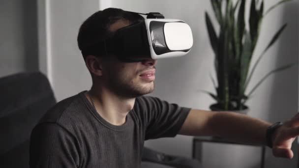junger bärtiger Mann mit Headset der virtuellen Realität im Büro sitzt auf einem Sofa und versucht, etwas zu berühren, das er in der virtuellen Welt sieht.