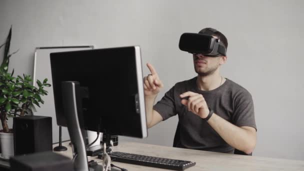 Young man wearing virtual reality goggles headset and sitting in the office against computer and trying to touch objects or control VR with a hand. Connection, technology, new generation.
