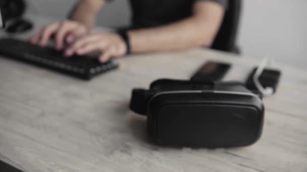 Die Hände der Männer nehmen ein Vr-Headset zur Benutzung. Virtual-Reality-Brillen liegen auf einem Tisch. moderne Technologien. das Konzept der Zukunftstechnologie.