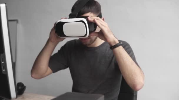 junger Mann beginnt mit Virtual-Reality-Brille Headset und sitzt im Büro gegen Computer. Verbindung, Technologie, neue Generation. Mann versucht, Gegenstände zu berühren oder vr mit einer Hand zu steuern.