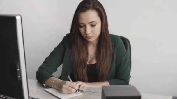 Egy üzletasszony ír valamit a füzetébe. Vállalkozást indító női vállalkozó diák, aki jegyzeteket tanul a számítógép közelében lévő munkahelyén. Egy nő kézírása egy fehér üres jegyzetfüzetre az asztalon..