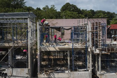 PHUKET, THAILAND - FEBRUARY 10, 2019. Workers work on the new under construction building. Under-construction of concrete building of a new multi storage building.