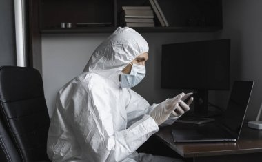 Man in protective suit, medical mask and rubber gloves sits at home and using a phone for chatting with a friends or business partners during quarantine. Man at remote work in a pandemic covid