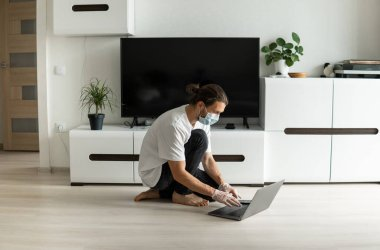 Man in medical mask is sitting on a floor in his living room and working from home with a laptop because of coronavirus. Remote work during pandemic. Stay home during COVID-19 quarantine. Freelancer.