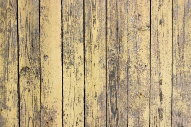 Background of wooden boards with a cracked mustard color paint.
