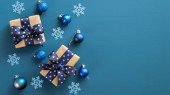 Elegantní vánoční kompozice. Na modrém pozadí ležely ploché dárkové krabice s modrou stuhou, modrými koulemi a sněhovými vločkami. Vánoční banner maketa s moderními dekoracemi. Horní pohled, kopírovací prostor