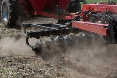 Closeup view of working discs harrow in row placed in ground of green field