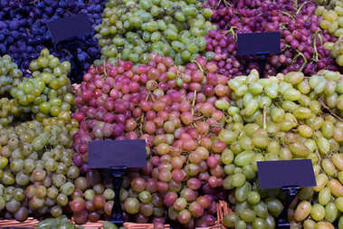 Close up of grapes in bunches in wooden baskets in store