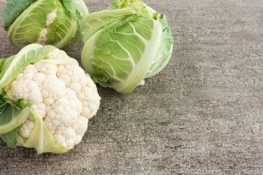Composition of Three Whole Cauliflowers on Brown