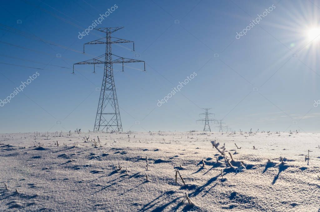 A line of high-voltage gears on a white snow-covered field in a