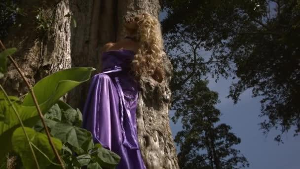 Mladá žena s kudrnatými blond vlasy v elegantních fialových šatech pózuje v blízkosti velkého stromu a těší moment. Zelené stromy a listy na pozadí.