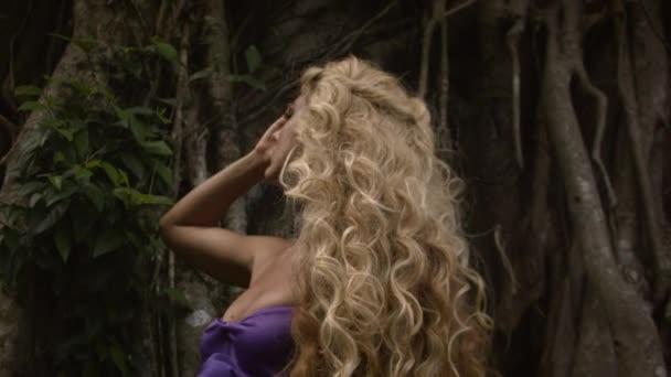 junge sinnliche Frau mit lockigem blondem Haar in elegantem lila Kleid posiert in der Nähe eines großen Baumes und genießt den Moment. filmische Wurzeln und Laub im Hintergrund