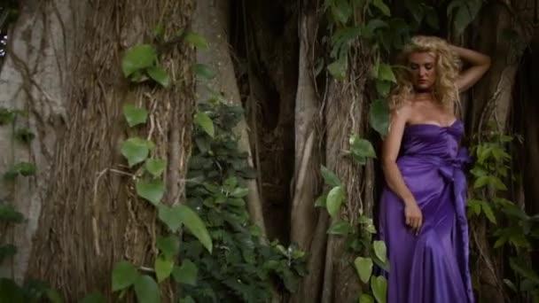 Mladá vážná žena s kudrnatými blond vlasy v elegantních fialových šatech pózuje poblíž velkého stromu v tropickém lese. Dramatické kořeny a listoví.