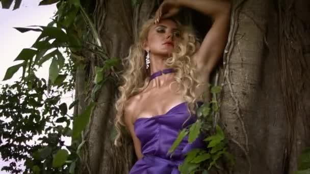Fiatal gondolkodó nő göndör szőke haj elegáns lila ruhát pózol közel nagy fa trópusi erdőben. Filmgyökerek és lombozat a háttérben.