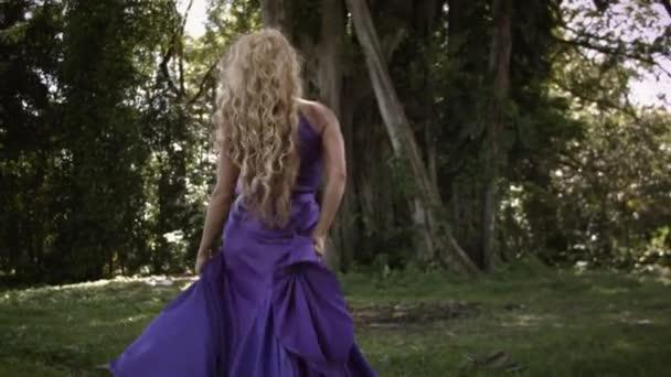 junge schöne Frau mit lockigem blondem Haar in elegantem lila Kleid, die auf einer Wiese neben einem großen Baum mit grünem Laub im tropischen Wald spaziert und posiert.