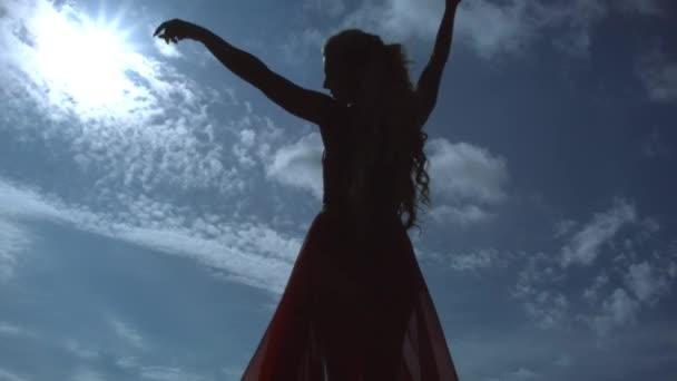 Silhouette einer jungen Frau mit blonden Locken im eleganten langen roten Kleid, die auf einer Klippe posiert und die Hände vor dem Hintergrund von Himmel und Sonne in die Höhe reckt.