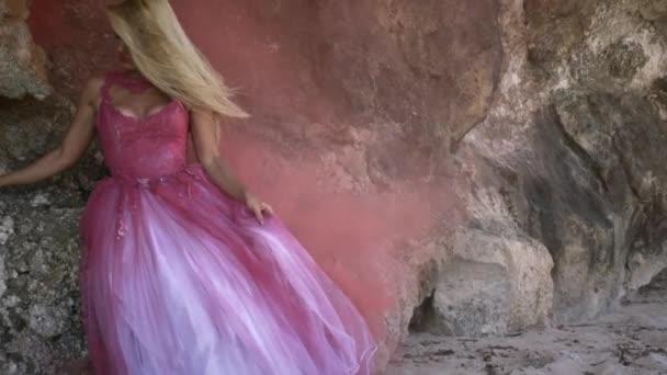 Mladá romantická žena s blond vlasy v růžové načechrané šaty stojící na písku a pózující na pozadí velké skály a hustý kouř.