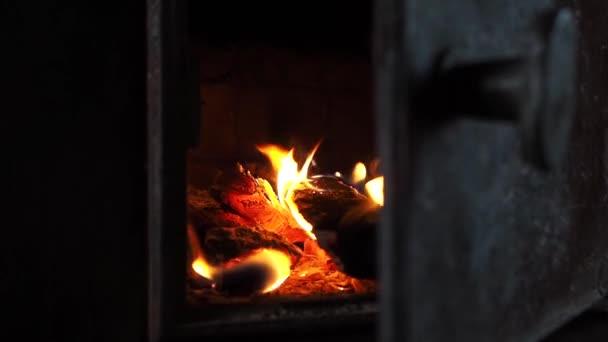 Dřevo hořící v litinovém sporáku, zblízka. Vytápění venkovského domu s kamny. Otevřenými dveřmi pece vyšlehly jasné plameny. Koncept oteplování v zimě u krbu.